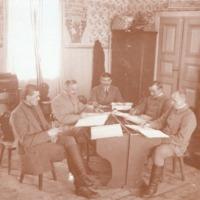 Ryhmäkuva, pöydän ympärillä viisi miestä