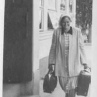 Katri Väisänen matkalla mahdollisesti junaan Savonkadulla keskellä kesäpäivää 1950-luvulla